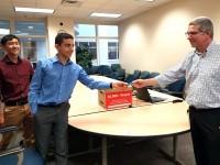 Nathan Koh and Yousef Emara present 50,000 signatures to MDEQ's Matt Gamble.