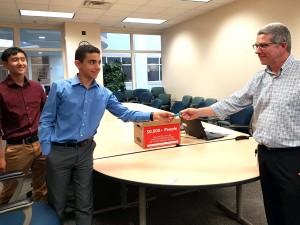 Nathan Koh and Yousef Emara present 50,000 signatures to MDEQ's Matt Gamble.